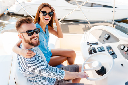 nautical vessels: Starting their summer vacation. Top view of young couple looking at camera and smiling while driving yacht