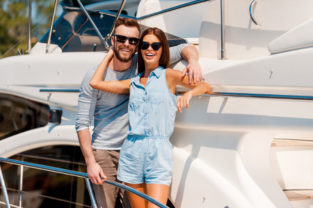 heterosexual couple: We are always happy together. Happy young couple looking at camera and smiling while standing on the deck of yacht Stock Photo