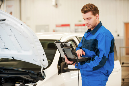 computer services: Mechanic examining car. Confident young man working on special laptop while standing in workshop near a car Stock Photo