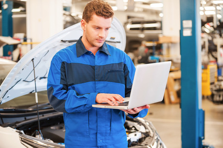 using computer: Mechanic with laptop. Confident young man working on laptop while standing in workshop with car in the background Stock Photo