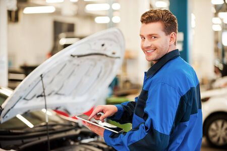 workshop service: Years of mechanical experience. Confident young man working on digital tablet and smiling while standing in workshop with car in the background Stock Photo