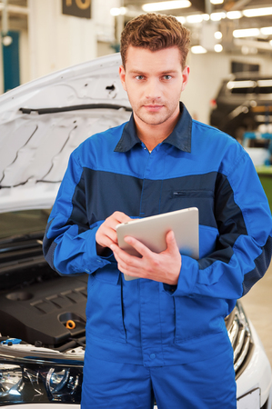 only adult: Concentrated on your problem. Confident young man working on digital tablet and looking at camera while standing in workshop with car in the background
