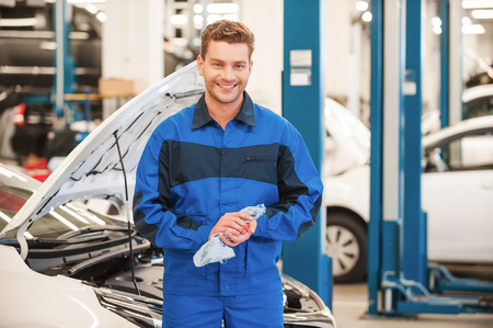 auto repair: After the work is done. Confident young man in uniform wiping his hands with rag and smiling while standing in workshop with car in the background Stock Photo