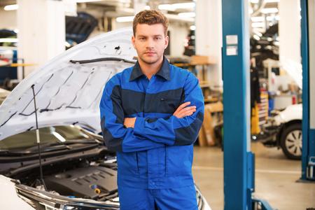 mecanico: Mecánico confiado y concentrado. Confiamos en el hombre de mantenimiento de jóvenes brazos cruzados y mirando a la cámara mientras está de pie en el taller con el coche en el fondo