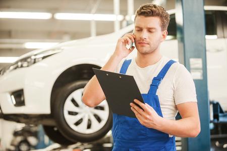 mecanico: Discutir algunos problemas con el coche. Apuesto joven hablando por teléfono móvil y mirando al portapapeles mientras está de pie en el taller con el coche en el fondo Foto de archivo