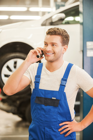 car mechanic: Your car is like a new! Handsome young man talking on the mobile phone and smiling while standing in workshop with car in the background Stock Photo