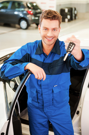Take your car. Cheerful young man in uniform stretching out hand with keys while standing near the car at workshop photo