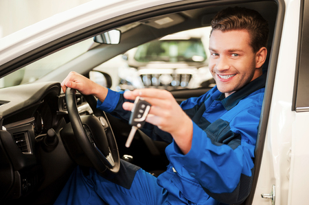 The work is done. Cheerful young man in uniform stretching out hand with keys while sitting in a car at workshop photo