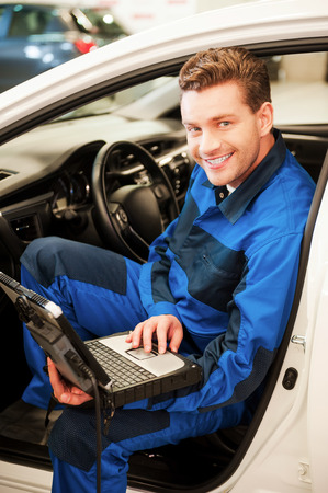 Examining car with special computer. Confident young man working on special laptop while sitting in a car in workshop photo