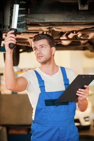 defects: Checking everything for defects. Confident young man in uniform holding lamp while standing underneath a car in workshop