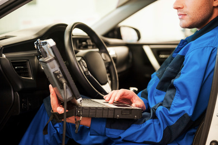 Man examining car. Confident young man working on special laptop while sitting in a car in workshop Foto de archivo