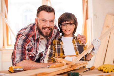 carpintero: Carpinter�a es una empresa familiar. Alegre carpintero var�n joven abrazando a su hijo mientras se apoya en la mesa de madera con diversas herramientas de trabajo que pone en ella Foto de archivo