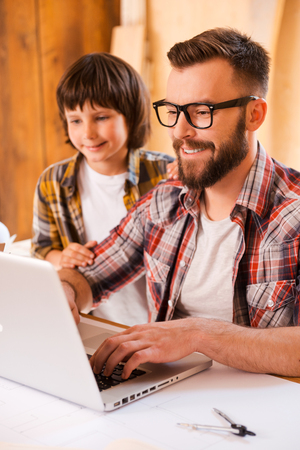 the place is important: Sharing an important experience. Smiling young man working on laptop with his son while sitting at the working place