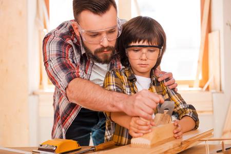 Erfolg ist eine erlernbare Fähigkeit. Konzentrierte junger männlicher Zimmermann seinen Sohn unterrichtet, mit Holz in seiner Werkstatt arbeiten Standard-Bild