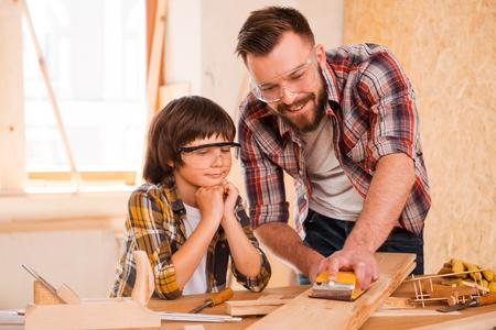 carpintero: Precisi�n y perfection.Smiling carpintero macho joven que muestra a su hijo c�mo la madera de arena en su taller Foto de archivo