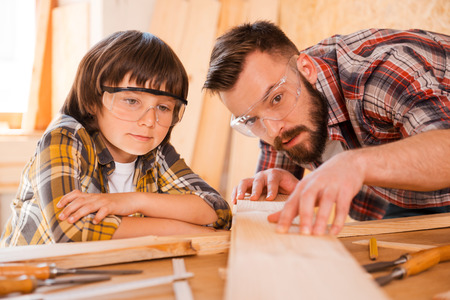 fathers: Precision is the most important part of carpentry. Concentrated young male carpenter showing his son how to work with wood in workshop