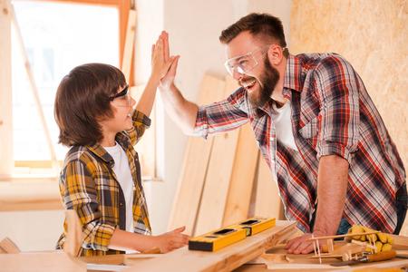 我々 はそれをやった!陽気な若い男性大工と彼の息子は、ワーク ショップでの作業中、お互いに高い 5 を与えること