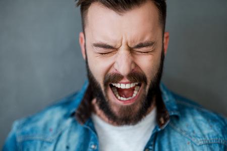 inteligencia emocional: Emociones desatadas. Hombre joven frustrado ojos manteniendo cerrados y la boca abierta mientras est� de pie contra el fondo gris