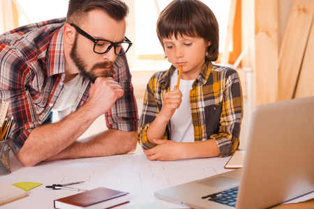 Family brainstorming. Thoughtful young man and his sonworking together while sitting at working place photo