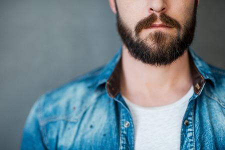 modelos hombres: Barba es su estilo. Recorta la imagen de hombre joven vestido con camisa de pie contra el fondo gris
