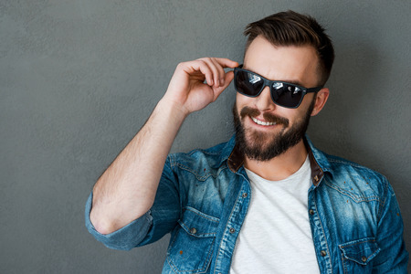 manly man: Rugged and manly. Smiling young man adjusting eyewear and looking away while standing against grey background