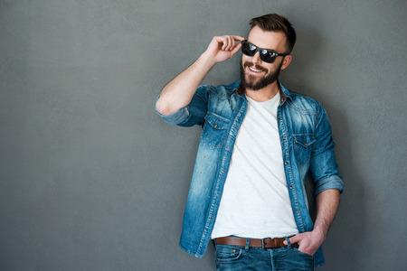Il a obtenu la personnalité charmante. Enthousiaste jeune homme ajuster lunettes et regarde au loin en se tenant debout sur fond gris Banque d'images - 40803911