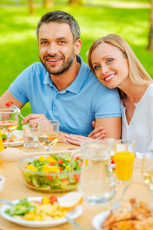 family eating: Top view of happy young loving couple enjoying meal together while sitting at the dining table outdoors Stock Photo