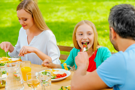 Young man feeding his daughter with salad while sitting together at the dining table outdoors photo