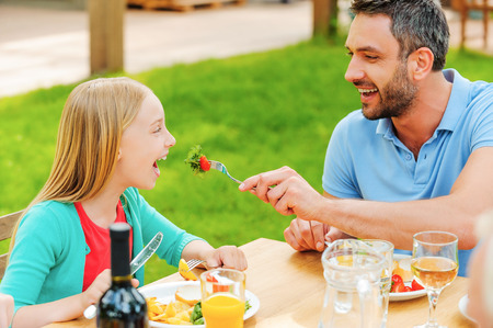 girl open mouth: Happy young man feeding his daughter with salad while sitting together at the dining table outdoors