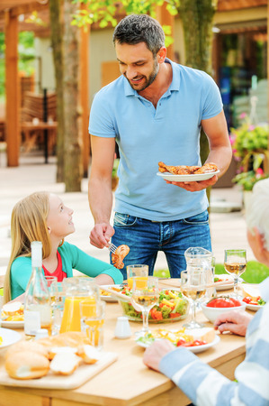 mixed age range: Young man putting grilled chicken to the plates while his family sitting at the dining table
