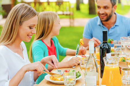drink food: Happy family enjoying meal together while sitting at the dining table outdoors