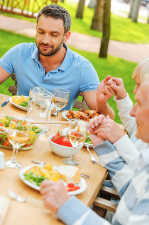 Family holding hands and praying before dinner while sitting at the table outdoors photo