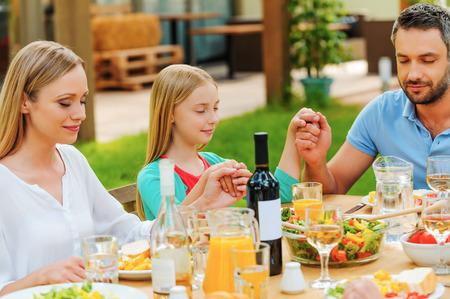 familia orando: Familia de la mano y rezando antes de la cena mientras se está sentado en la mesa al aire libre