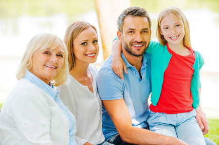 mixed age range: Enjoying time with family. Happy family bonding to each other and smiling while sitting outdoors together Stock Photo