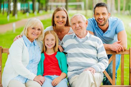 Gelukkig gezin. Gelukkig gezin van vijf mensen binding aan elkaar en glimlachen terwijl buiten zitten samen Stockfoto