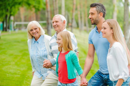 mixed age range: Quality time with family. Happy young family holding hands while walking outdoors together