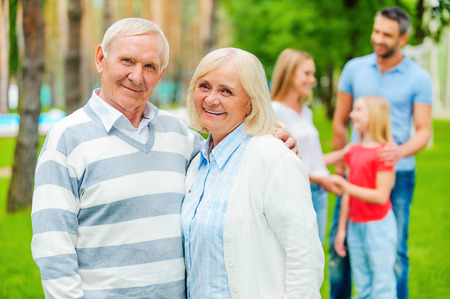 social gathering: Happy senior couple bonding and looking at camera while other family members standing in the background Stock Photo