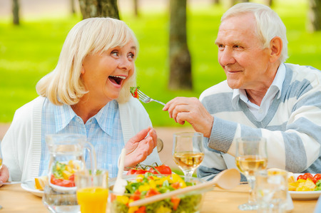 couple dining: Senior man feeding his cheerful wife with fresh salad while both sitting at the dining table outdoors