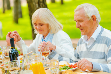 thanksgiving adult: Senior couple holding hands and praying before family dinner while sitting at the table outdoors Stock Photo