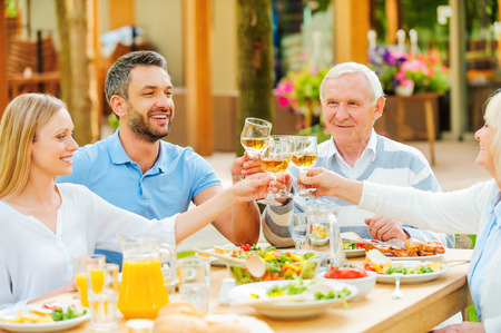 thanksgiving adult: Happy young and senior couples sitting at the dining table and toasting with wine