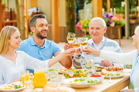comidas: Parejas jóvenes y mayores felices que se sientan en la mesa de comedor y brindando con vino