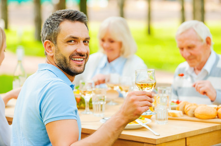 over eating: Happy young man toasting with wine and smiling while sitting together with his family outdoors Stock Photo