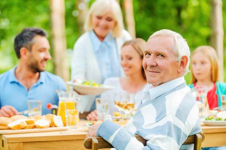 familia cenando: Familia feliz de cinco personas que se sientan en la mesa de comedor al aire libre mientras que el hombre mayor que mira por encima del hombro y sonriendo