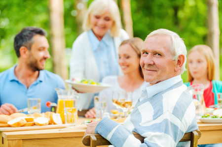 outdoor dining: Happy family of five people sitting at the dining table outdoors while senior man looking over shoulder and smiling