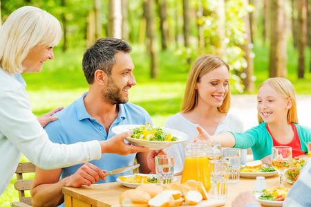 familia cenando: Familia feliz disfrutando de comida juntos mientras la mujer mayor que pasa un plato con ensalada a una ni�a