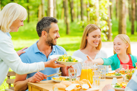 family dining: Happy family enjoying meal together while senior woman passing a plate with salad to a little girl Stock Photo