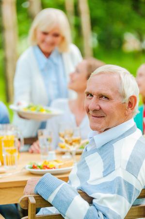 행복 한 가족 야외에서 식탁에 앉아 수석 남자 동안 어깨 너머로보고 웃 고