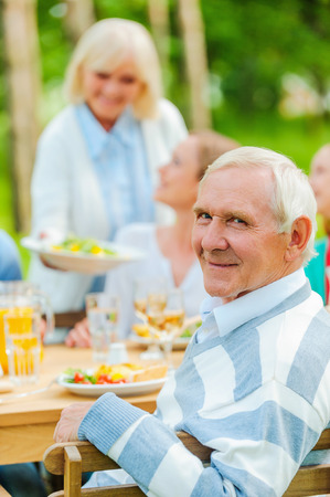 formal dinner: Happy family sitting at the dining table outdoors while senior man looking over shoulder and smiling