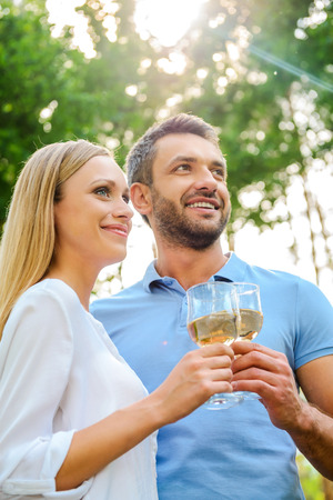 tomando vino: Ángulo de visión baja felices jóvenes amantes de la pareja la celebración de vasos de vino blanco y mirando a otro lado mientras está de pie cerca uno del otro al aire libre Foto de archivo