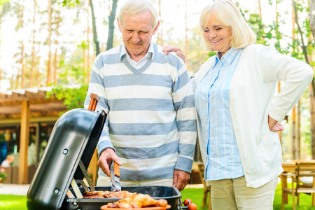 barbecuing: Happy senior couple barbecuing meat on the grill while standing at the back yard of their house